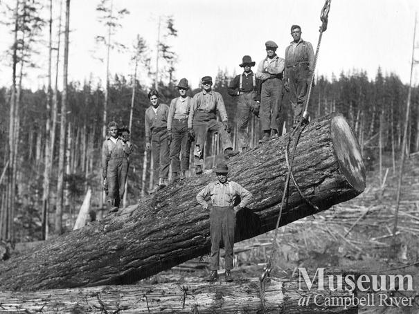 Loggers on a large fir log on its way to the log dump