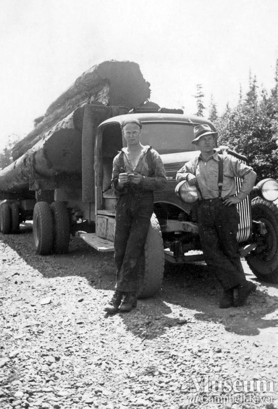 Loggers in front of loaded logging truck near Port Neville